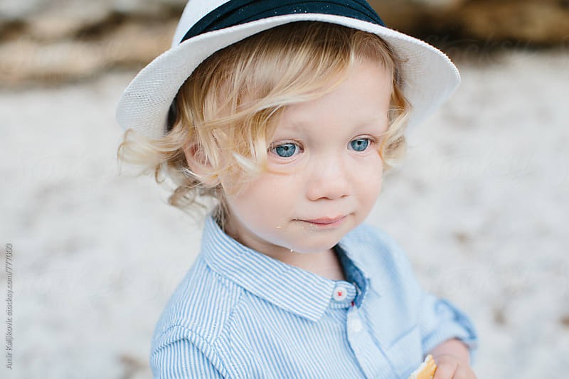 Cute little boy in a trendy sunhat by Amir Kaljikovic for Stocksy United