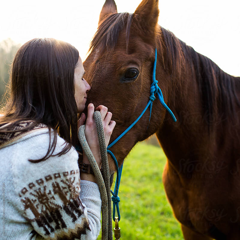 Woman making a gesture of affection to her horse by michela ravasio for Stocksy United
