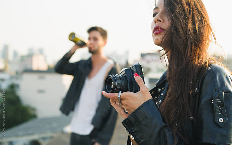 Girlfriend holding a retro camera and waiting for perfect moment on a rooftop. by Jovo Jovanovic for Stocksy United