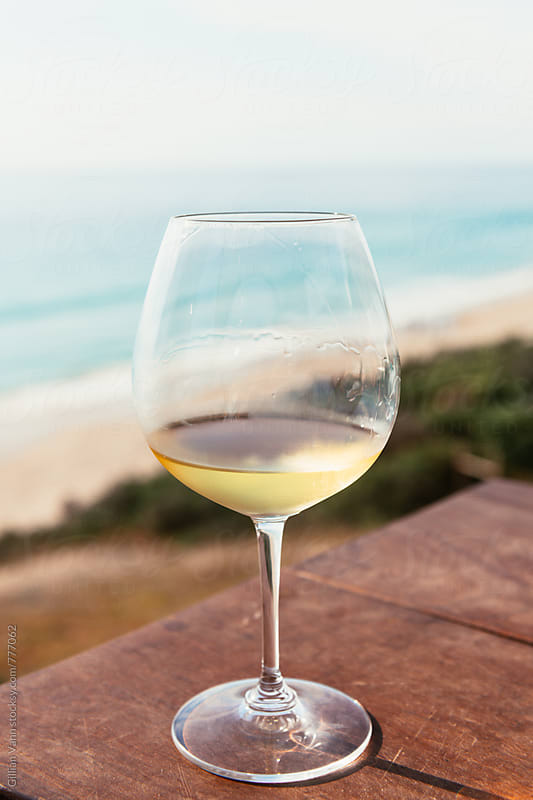 a glass of white wine by the ocean at Port Willunga in the McLaren Vale wine region by Gillian Vann for Stocksy United