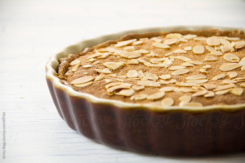 Whole Bakewell Tart with flaked almonds by Kirsty Begg for Stocksy United
