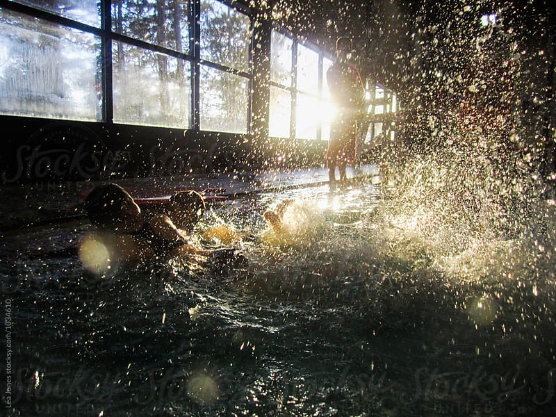 kids in an indoor pool splashing water by Léa Jones for Stocksy United