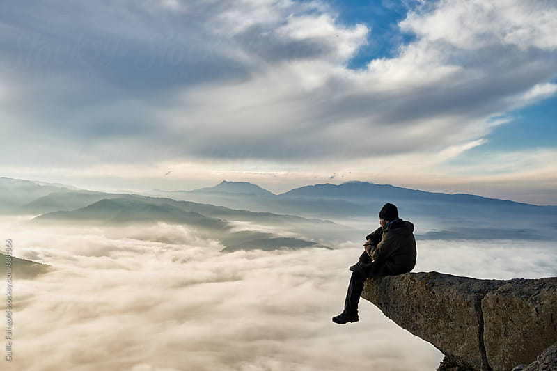Hiker sitting on the edge of a cliff over the clouds by Guille Faingold for Stocksy United