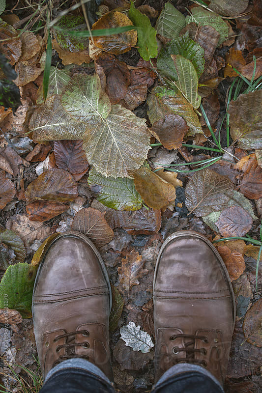 Overhead of a man boots on fall soil. by BONNINSTUDIO for Stocksy United