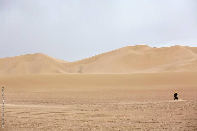 Man motorcycling through desert sand dunes by Laura Austin for Stocksy United