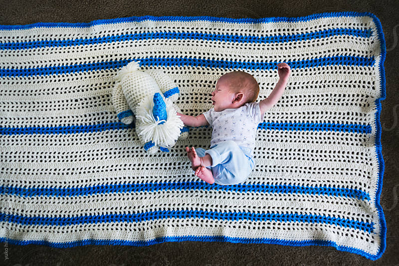 Newborn baby boy lying on a blue blancket with his staffed animal by yuko hirao for Stocksy United