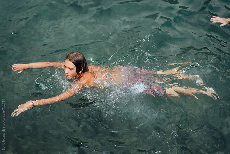 Boy swimming in the sea  by Boris Jovanovic for Stocksy United