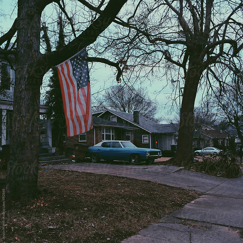 American flag with an old blue car in the background by Justin March for Stocksy United