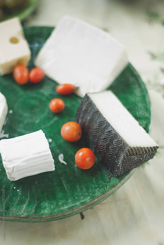 A variety of cheese and cherry tomatoes on a rustic green plate by Lydia Cazorla for Stocksy United