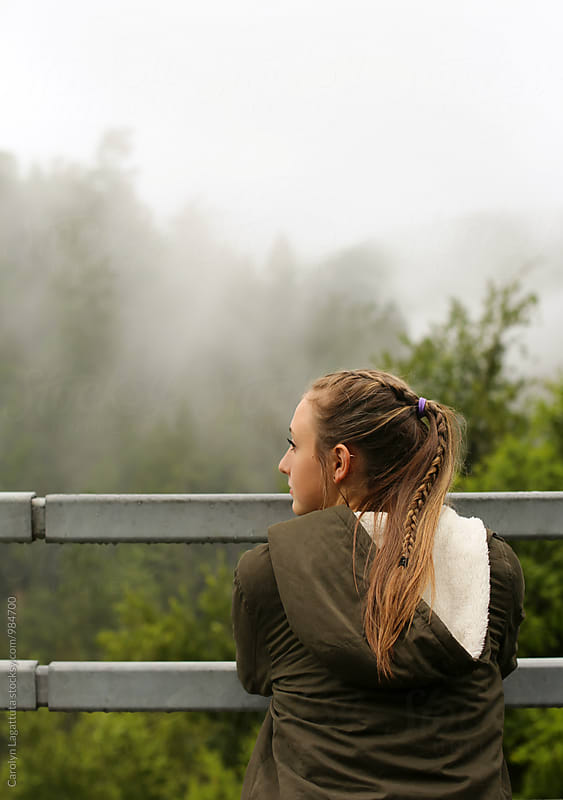 Teenage girl admiring a beautiful, foggy view by Carolyn Lagattuta for Stocksy United