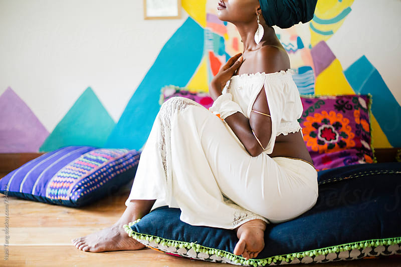 Young african woman sitting on the cushion floor in exotic colorful design space by Nabi Tang for Stocksy United