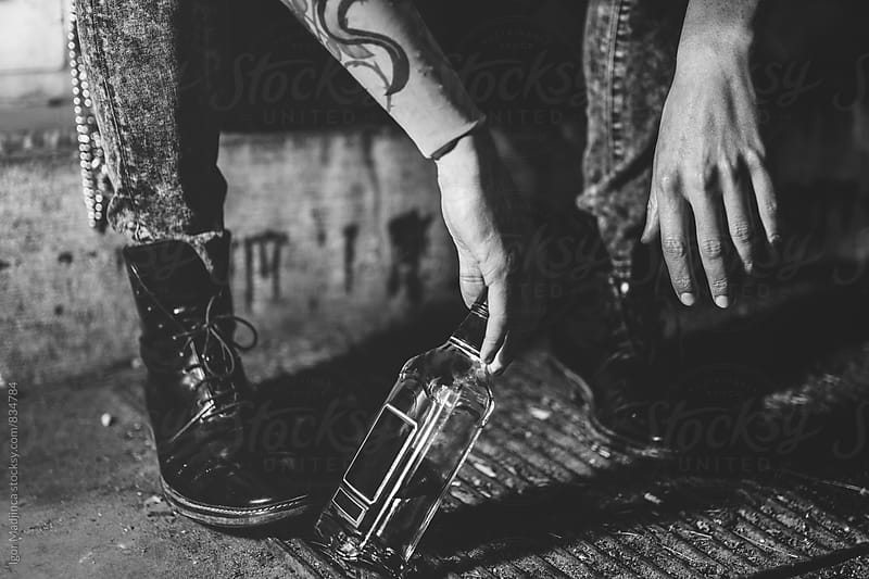 hangover,drunk person in jeans and boots on the street,addict, bottle of alcohol drink by Igor Madjinca for Stocksy United