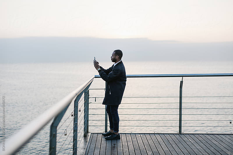 Side view of a man taking photo of the sea. by BONNINSTUDIO for Stocksy United