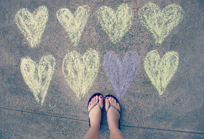 Feet standing near a bunch of chalk hearts - one of them different than the others by Carolyn Lagattuta for Stocksy United