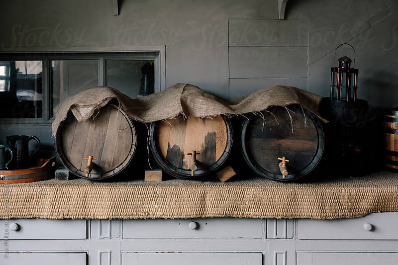 Three wooden antique beer barrels in period setting by Paul Phillips for Stocksy United