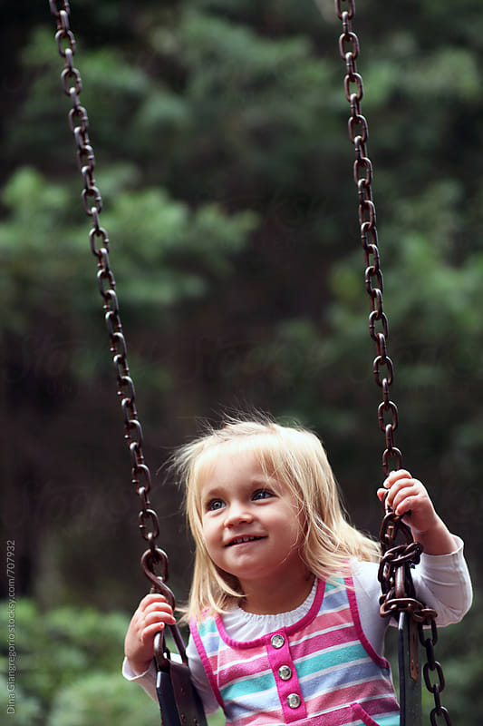 Toddler Girl Smiling While on Swing by Dina Giangregorio for Stocksy United