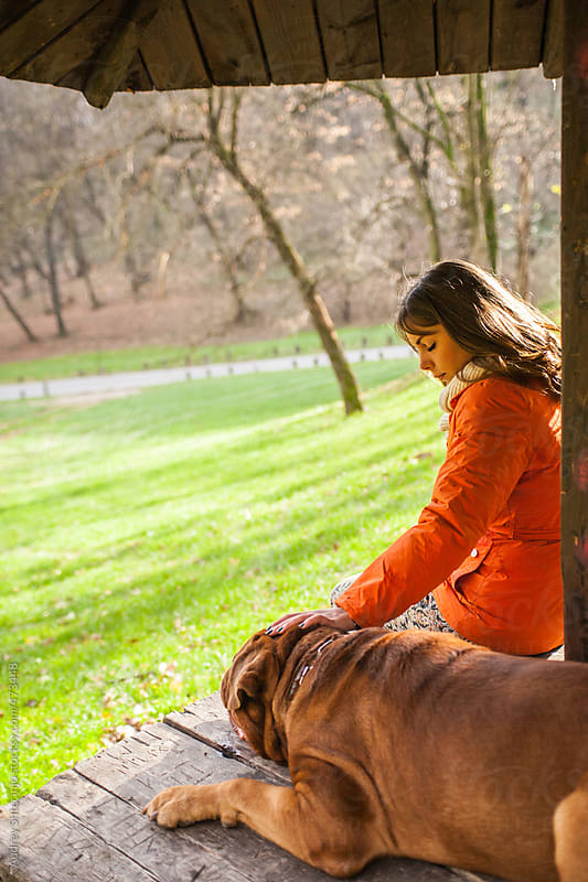 Girl and her dog resting on wooden bench in nature. by Audrey Shtecinjo for Stocksy United