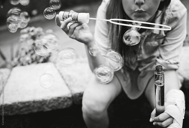 Young girl with a cast on her hand blowing bubbles by Carolyn Lagattuta for Stocksy United