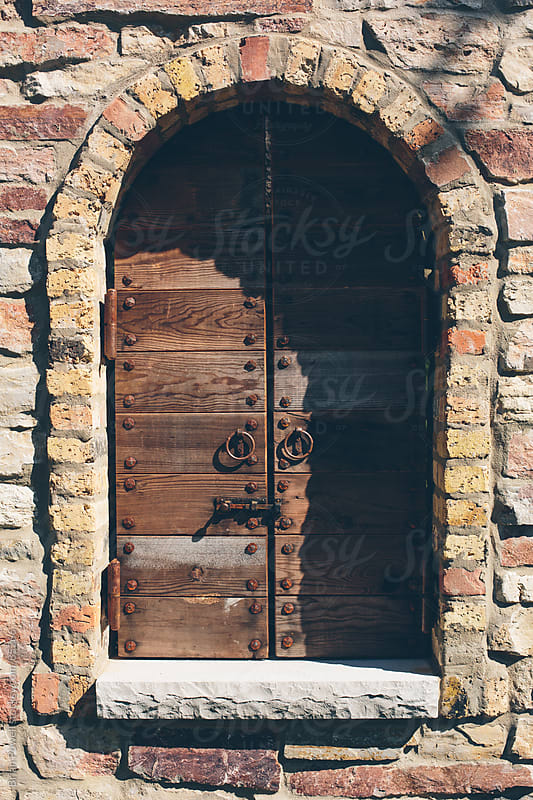 old wood shutters in arched window by Brian Powell for Stocksy United