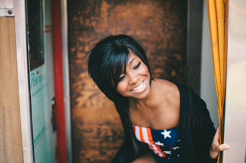 Black girl in Americana top smiling in a Photo Booth by Gabrielle Lutze for Stocksy United