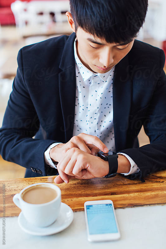 Businessman using his smart watch having breakfast in a coffee bar. by BONNINSTUDIO for Stocksy United