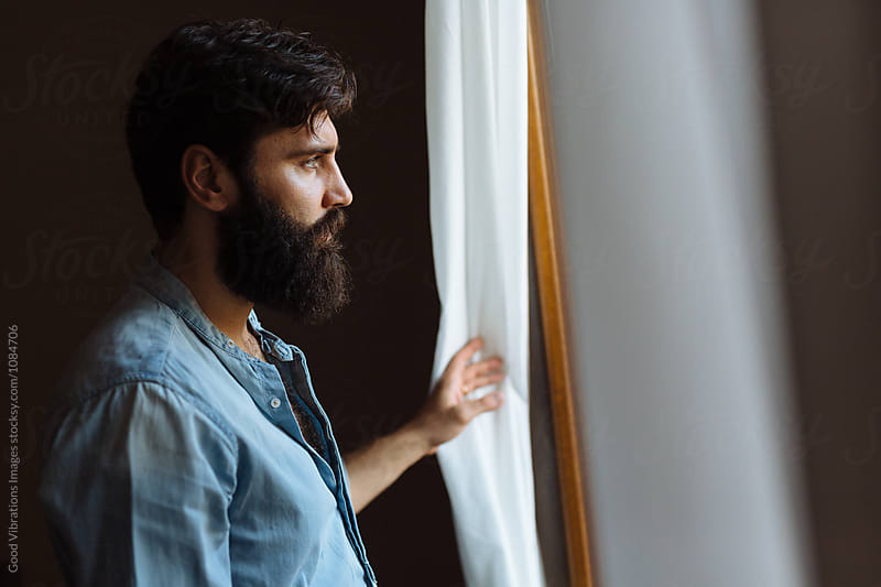 Bearded man looking out of the window by Good Vibrations Images for Stocksy United