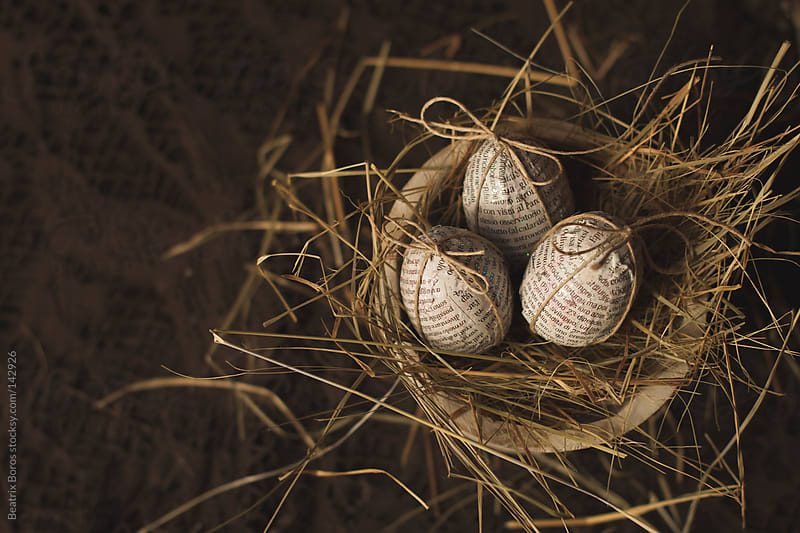 Rustic Easter eggs covered with newspaper decoupage in a bucket full of straw by Beatrix Boros for Stocksy United