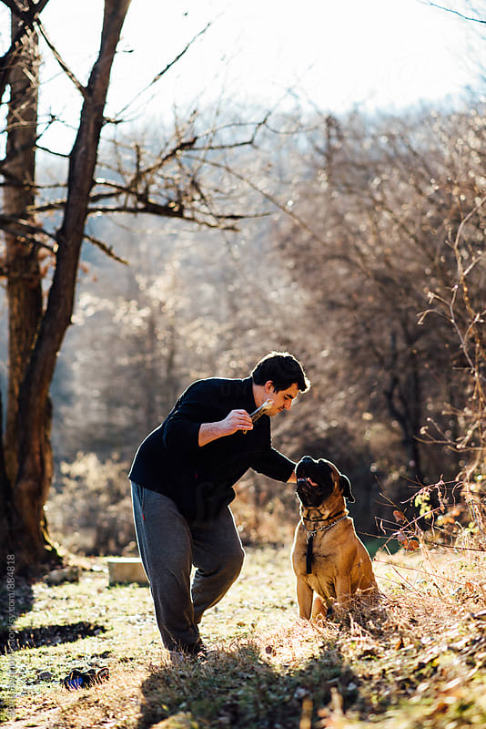Man enjoying a day with his dog by the river bank by Boris Jovanovic for Stocksy United