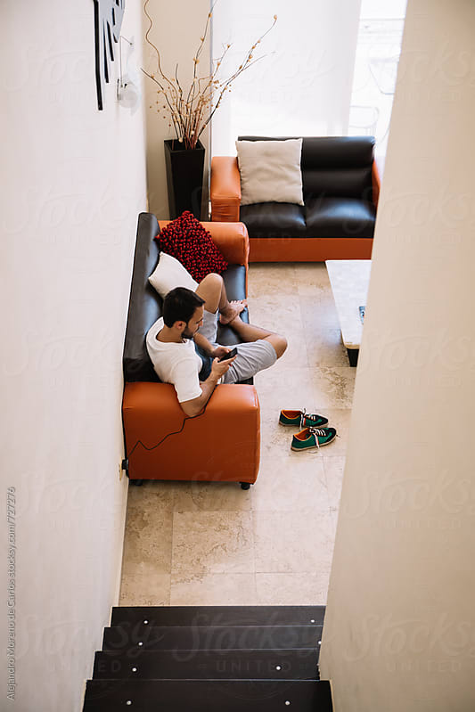 Young man checking his phone on the sofa of modern apartment by Alejandro Moreno de Carlos for Stocksy United