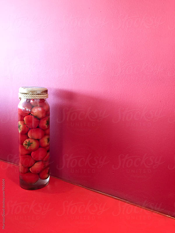 Tomatoes stores in a jar against a red background by Murtaza Daud for Stocksy United