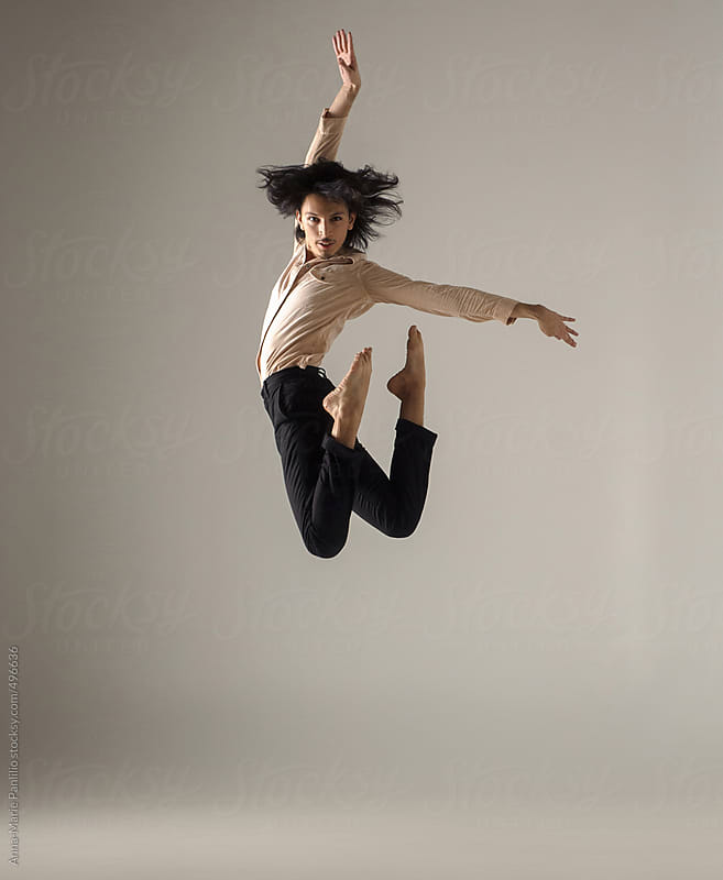 Male contemporary dancer leaping with hair flying by Anna-Marie Panlilio for Stocksy United