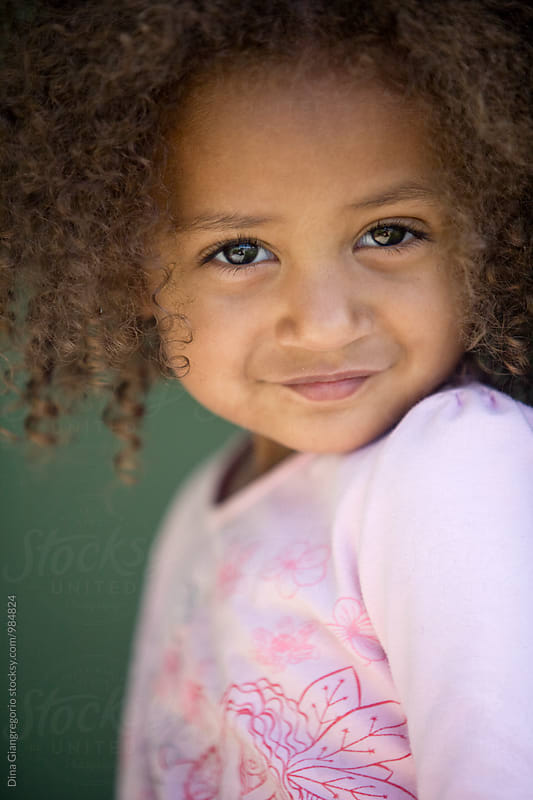 Portrait of Young African American Girl With Soft Smile by Dina Giangregorio for Stocksy United