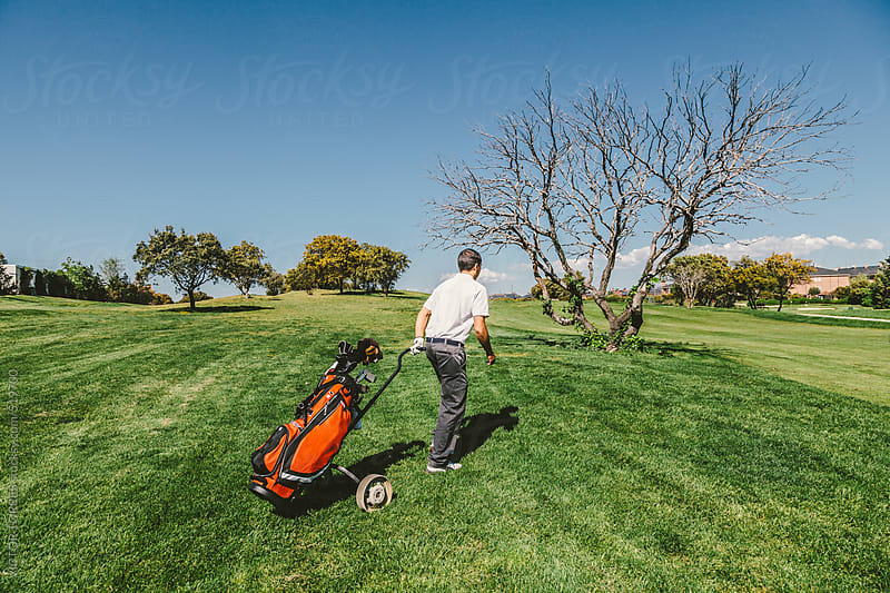 Man Walking Through a Golf Course  by VICTOR TORRES for Stocksy United