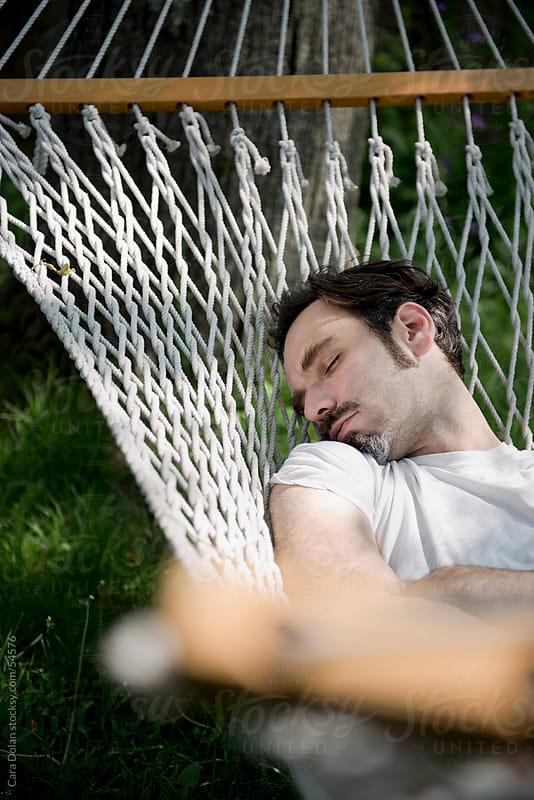 Man asleep in a hammock by Cara Slifka for Stocksy United