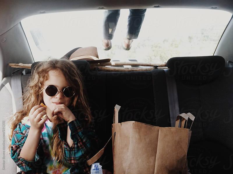Little Girl Eating Chips in the Car by Denise Bovee for Stocksy United