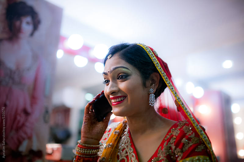 Beautiful young woman talking on mobile on her marriage ceremony at the parlour by Apratim Saha for Stocksy United