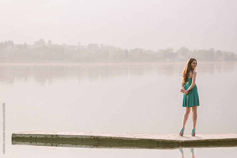 Young woman on a small pier by michela ravasio for Stocksy United