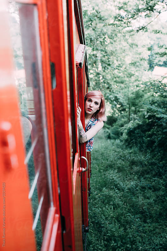 woman poking out a funicular window by Thais Ramos Varela for Stocksy United