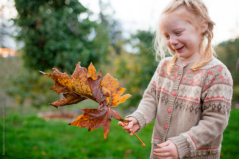 A little Girl Holds giant Leaves and smiles by Amanda Voelker for Stocksy United