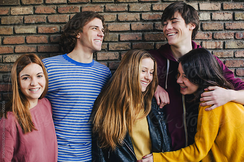 Portrait of teenage friends smiling in front of a brick wall. by BONNINSTUDIO for Stocksy United