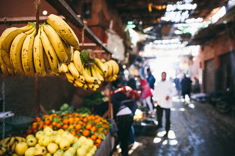 Banana bunches hanging on counter at Moroccan market by Alejandro Moreno de Carlos for Stocksy United