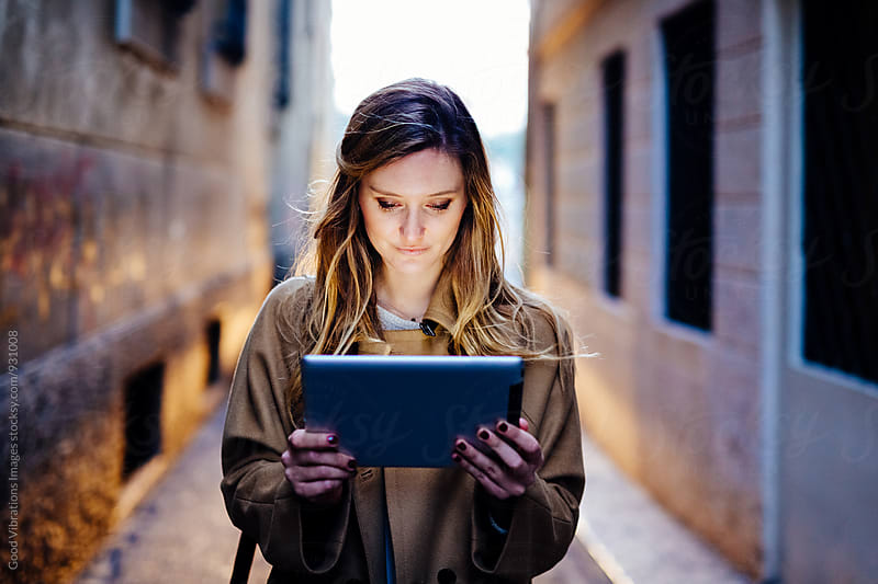 Woman holding a digital device in a dark alley by Good Vibrations Images for Stocksy United