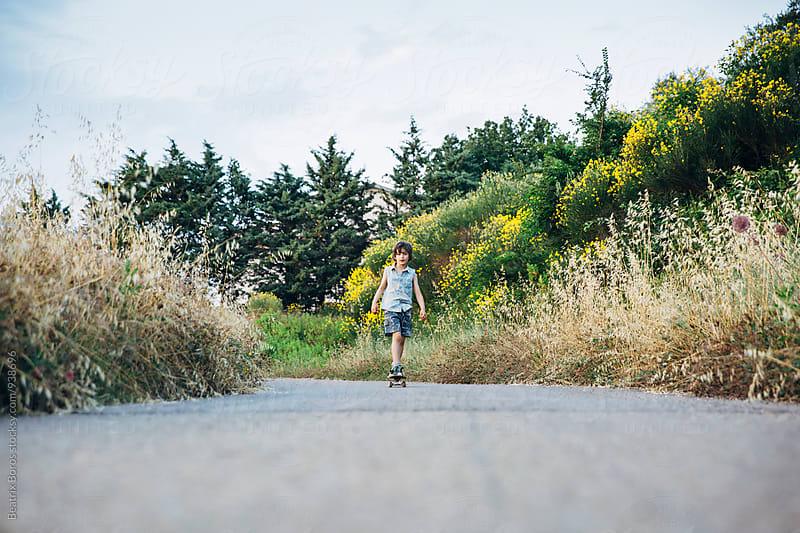 Child skateboarding on the asphalt outdoors by Beatrix Boros for Stocksy United