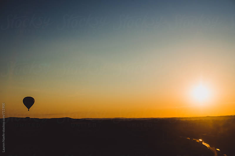 Hot air balloon and sun against colorful sky by Lauren Naefe for Stocksy United