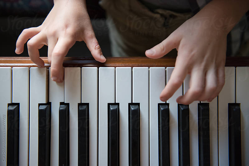 Child is learning to play the piano by Cara Dolan for Stocksy United