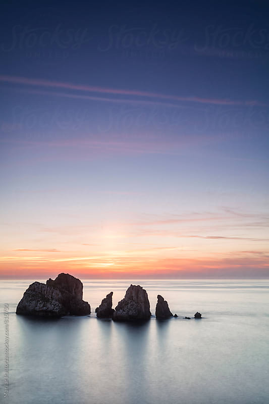 Rocks in the ocean at sunset by Marilar Irastorza for Stocksy United