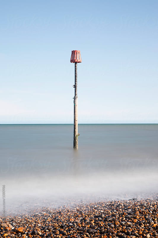 Tidal marker in the sea by James Ross for Stocksy United