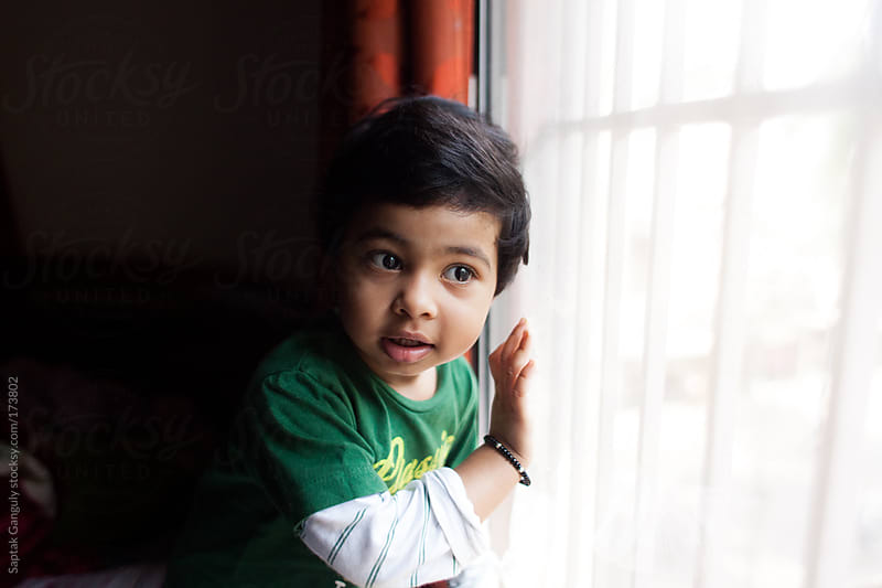 Toddler looking through a glass window by Saptak Ganguly for Stocksy United
