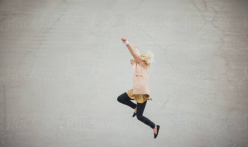 Woman jumps into air with joy  by Drew Schrimsher for Stocksy United