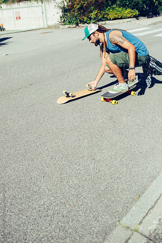 Skater picking up a skateboard on the street by michela ravasio for Stocksy United